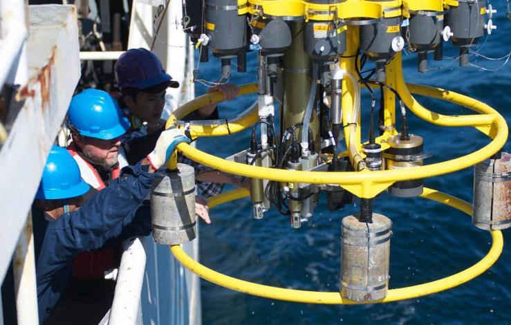 Two men who hard hats pull in a CTD rosette from the ocean.
