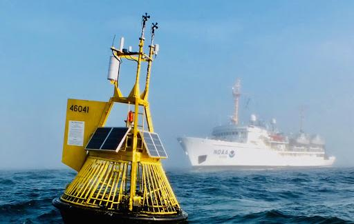 An yellow ocean acidification buoy located in the Pacific Ocean off the central Washington coast with the NOAA Ship Fairweather in the background.