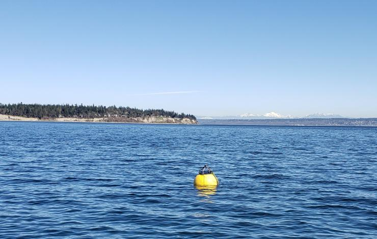 Yellow surface buoy floating in the water during testing of the first flotation controllable ocean mooring system