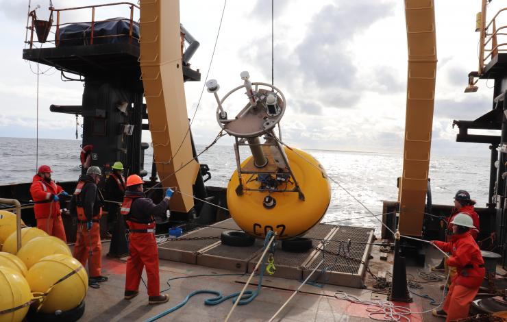 Yellow surface buoy being pulled up on to the back deck of a NOAA Ship by crew and scientists in life jackets.
