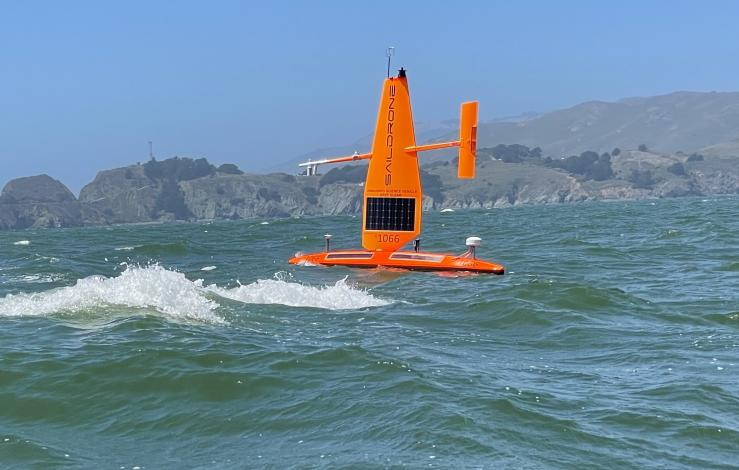 orange sailing drone in on the water with some waves sailing in front of San Francisco bluffs