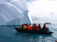 photo of a boat approaching an iceberg in Antarctica