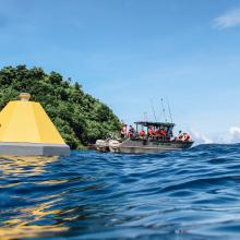 Buoy in Fagatele Bay in the NOAA National Marine Sanctuary of American Samoa with partner ship in the background..