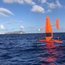 Orange drone with sail in open water in front of some bluffs and coastal city  in the distance