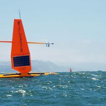 Two orange saildrones in the Pacific Ocean with San Francisco in the background.