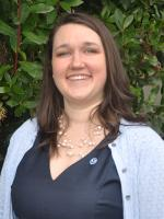 Jessica Cross standing in front of green shrub smiling with her NOAA pin on a blue shirt and blue cardigan
