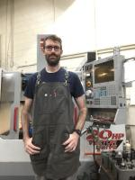 Sean standing in front of machine with grey work apron and glasses on